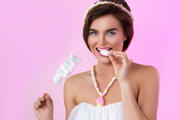 Feliz mulher bonita com marshmallows no espeto