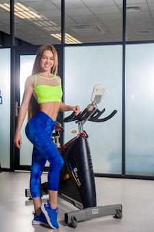 Feliz mulher bonita. exercite-se na academia. mulher sorrindo. bicicleta.