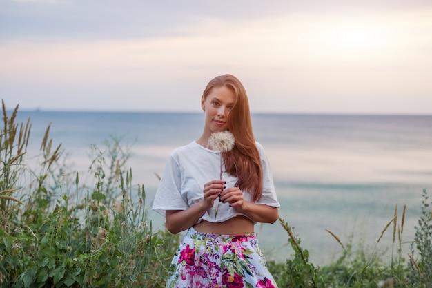 Feliz, mulher bonita, soprando, dandelion
