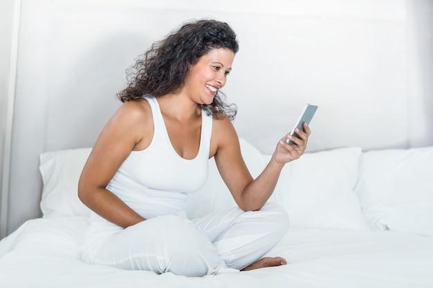 Feliz, mulher bonita, usando, telefone móvel