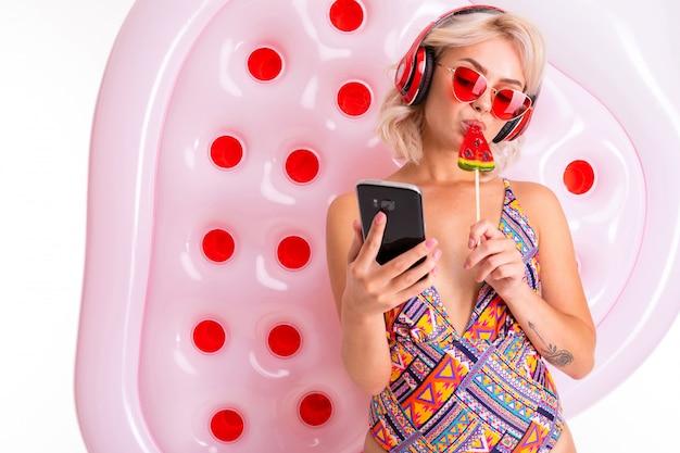 Feliz mulher branca loira fica de maiô com colchão de borracha grande, lolipop de melancia, telefone, fones de ouvido e sorrisos isolados