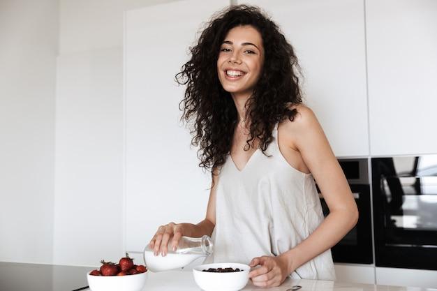 Feliz mulher cacheada de 20 anos tomando café da manhã doce no interior da cozinha e despejando leite no prato com granola