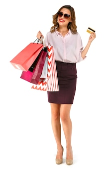 Feliz mulher casual usando óculos escuros, de pé e segurando sacolas coloridas