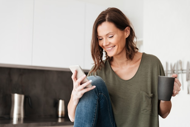 Feliz mulher casual usando smartphone e tomando café em casa