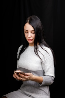 Feliz mulher caucasiana de beleza olhando para o telefone e escrevendo uma mensagem em fundo preto.