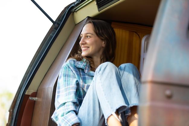 Feliz mulher caucasiana viajante curtindo férias na natureza no carro