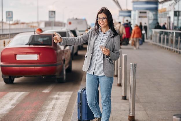 Feliz mulher caucasiana viajante no terminal do aeroporto está pegando um táxi
