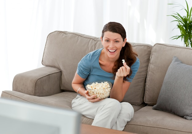 Feliz mulher com pipoca enquanto vê um filme na televisão