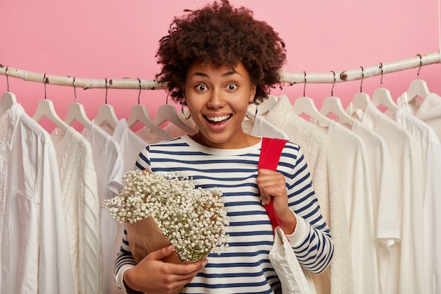 Feliz mulher de aparência agradável com penteado afro, visita loja de roupas, sorri feliz, carrega sacola de compras, fica em pé entre vestidos brancos em cabides