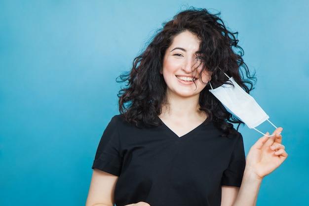 Feliz mulher de cabelo preto feliz decolando máscara antiviral médica.
