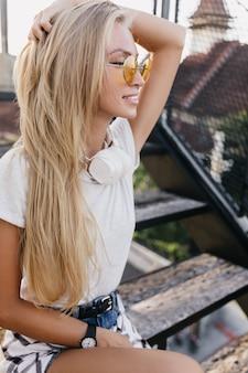 Feliz mulher de cabelos compridos em óculos de sol amarelos, sentado na escada. agradável menina caucasiana com cabelo loiro, relaxando na rua.