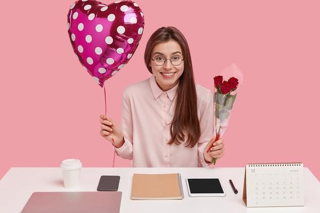 Feliz, mulher de cabelos escuros tem expressão alegre, sente prazer em receber um presente, carrega namorados e rosas vermelhas