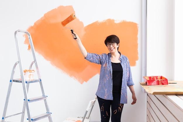 Feliz mulher de meia-idade pintando a parede interior com rolo de pintura na casa nova. uma mulher com rolo aplicando tinta na parede.