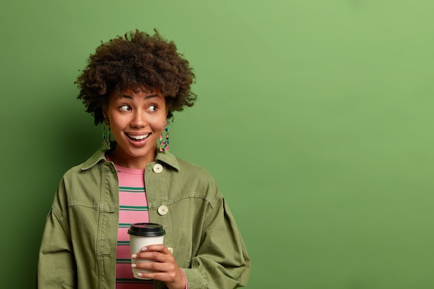 Feliz mulher de pele escura segura um copo descartável de bebida quente, olha para o lado e sorri feliz, faz uma pausa para o café, aprecia a bebida com cafeína matinal, isolado na parede verde, copie o espaço