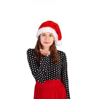 Feliz mulher de vestido sopra um beijo do ar para a câmera. garota emocional no chapéu de natal papai noel isolado