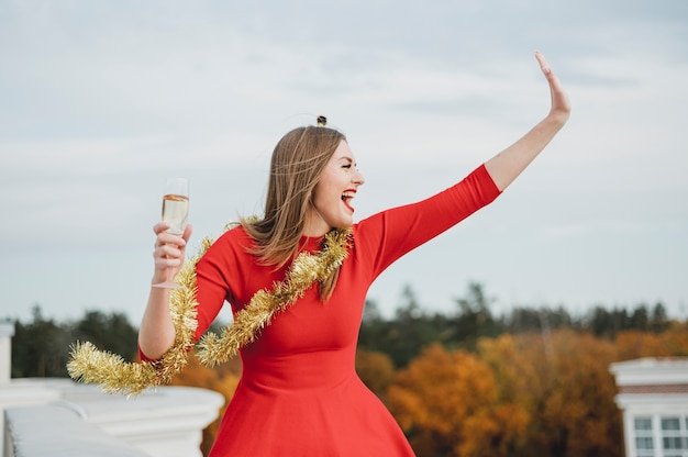 Feliz mulher de vestido vermelho, festejando no telhado