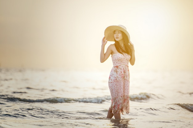 Feliz mulher despreocupada, apreciando o belo pôr do sol na praia