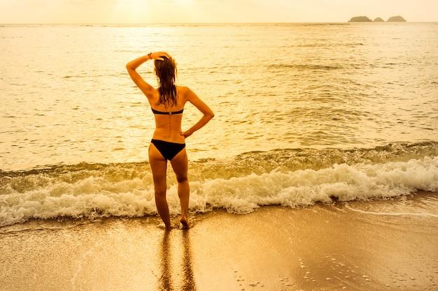 Feliz mulher despreocupada em bikini, apreciando o pôr do sol