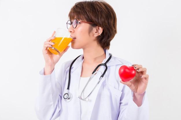 Feliz, mulher, doutor, segurando, a, vermelho, coração, e, suco laranja