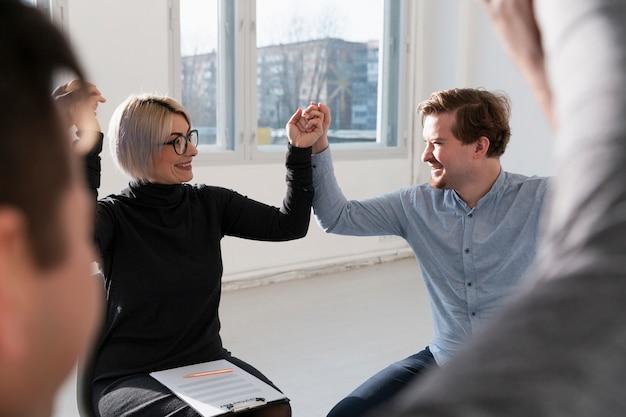 Feliz mulher e homem levantando as mãos e olhando um ao outro