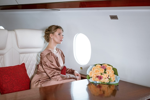 Feliz mulher elegante, sentado em um avião particular para a janela
