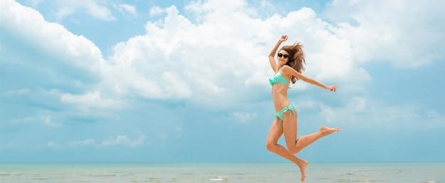 Feliz, mulher, em, biquíni, pular, praia, em, verão