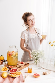Feliz mulher em pé dentro de casa bebendo bebida cítrica