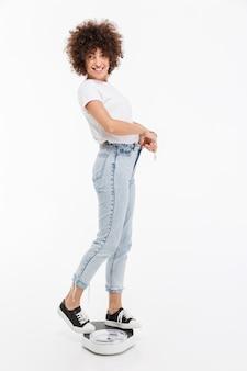 Feliz mulher em pé na balança e mostrando as calças soltas