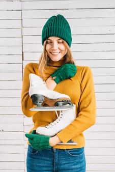 Feliz, mulher, em, suéter, segurando, patins