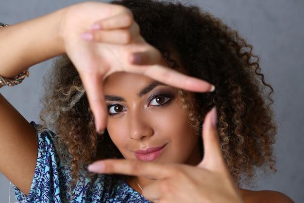Feliz mulher encaracolada fazendo quadrados com os dedos antes do rosto