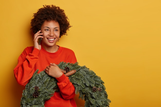 Feliz mulher encaracolada gosta de conversa ao telefone, discute a preparação para o natal com um amigo, segura coroa de abeto feita à mão com pinhas e fica contra um fundo amarelo