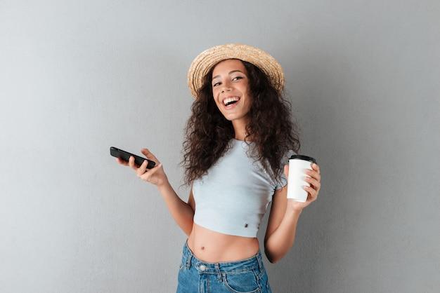Feliz mulher encaracolada no chapéu segurando smartphone e xícara de café