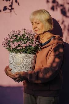 Feliz mulher envelhecida carregando o pote com flores. mulher idosa alegre em agasalhos elegantes e sorrindo