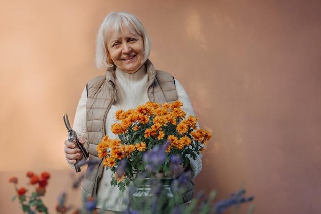 Feliz mulher envelhecida trabalhando com flores desabrochando no jardim. aposentada feminina sênior positiva