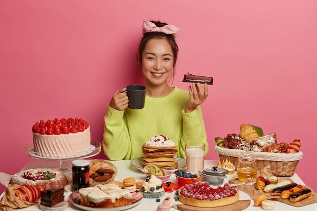 Feliz mulher étnica segura pedaço de bolo de chocolate, bebe chá com sobremesa, comemora feriado em casa com deliciosa comida doce, obtém prazer e gozo de sabor inesquecível.