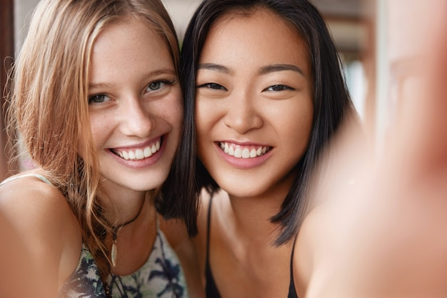 Feliz mulher europeia abraça o melhor amigo asiático, faça selfie, fique perto um do outro.