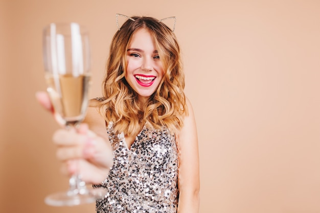 Feliz mulher europeia com cabelo loiro encaracolado levantando um copo de vinho com um sorriso na parede de luz