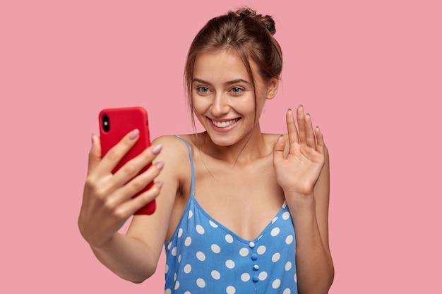 Feliz mulher européia com sorriso agradável, acenando com a mão do celular, vestida com vestido de bolinhas