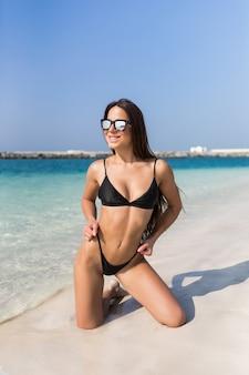 Feliz, mulher, ficar de joelhos usar biquíni preto na praia do oceano costa