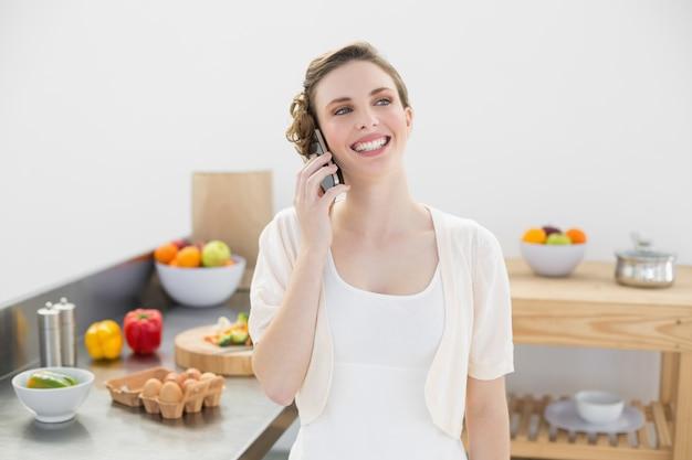 Feliz, mulher fofa telefonando em sua cozinha