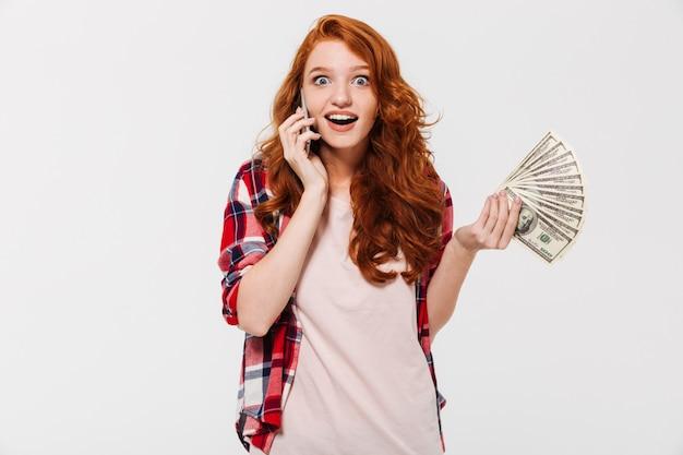 Feliz mulher gengibre chocada na camisa falando pelo smartphone, mantendo o dinheiro e olhando