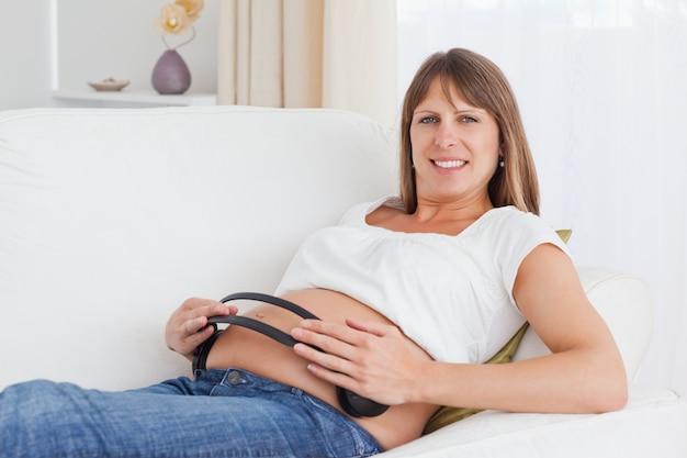 Feliz mulher grávida com fones de ouvido na barriga