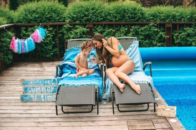 Feliz mulher grávida e sua pequena filha relaxando na cama de sol