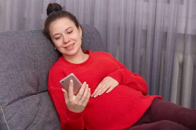 Feliz mulher grávida segurando o telefone inteligente, vestindo leggins e blusa vermelha, tem um monte na cabeça, baseia-se no sofá