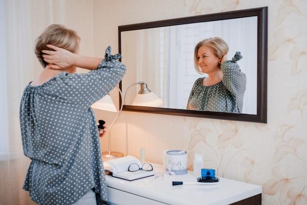Feliz mulher idosa de meia idade preens e ajusta o cabelo na frente do espelho da penteadeira