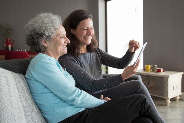 Feliz mulher idosa e sua filha navegando no computador tablet