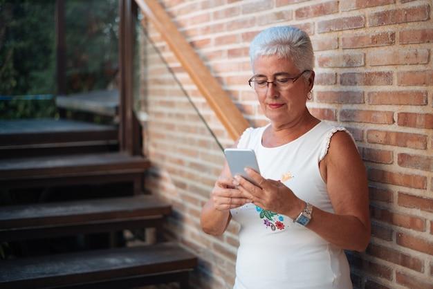 Feliz mulher idosa no telefone celular