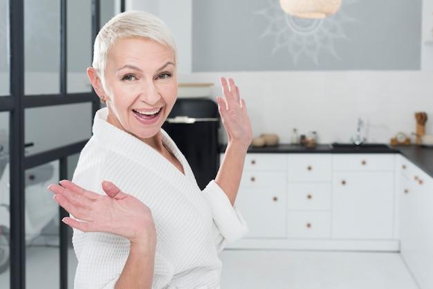 Feliz mulher idosa posando de roupão na cozinha