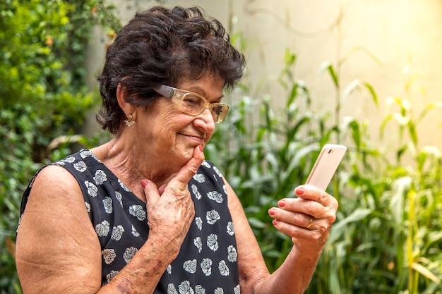 Feliz, mulher idosa, usando, cellphone