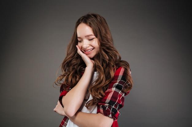 Feliz mulher jovem bonita camisa xadrez em pé e rindo